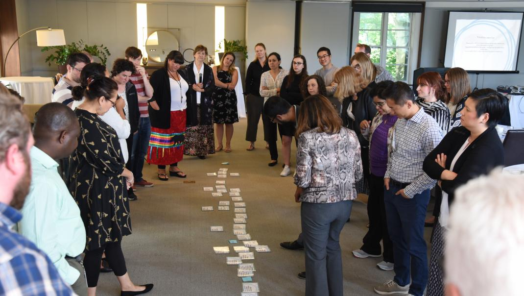 EN: People standing in a circle looking at cards on the floor FR: Les gens se tiennent en cercle en regardant des cartes sur le sol