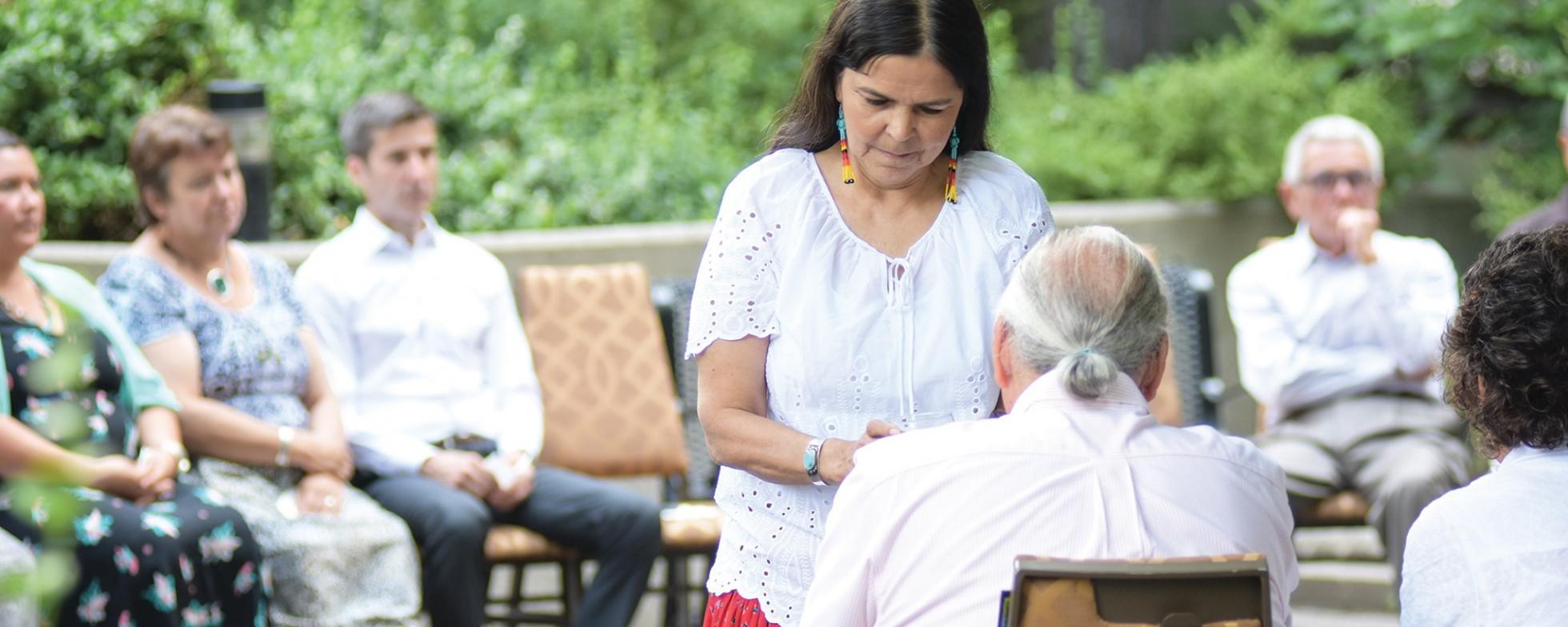 EN: A women is standing in front of a seated elderly man FR: Une femme se tient devant un homme âgé assis